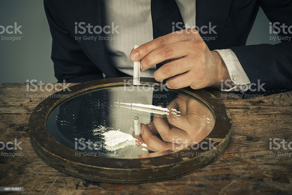 Businessman snorting cocaine stock photo