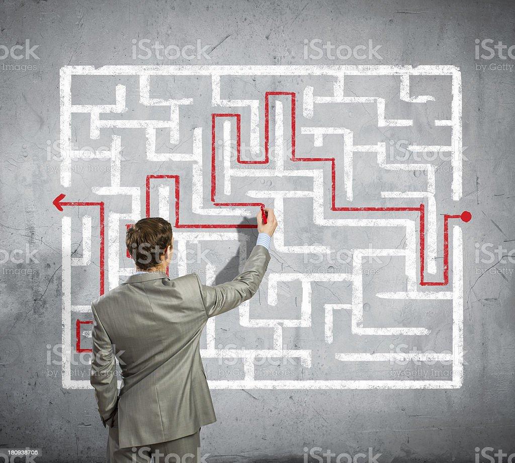 Businessman solving labyrinth problem royalty-free stock photo