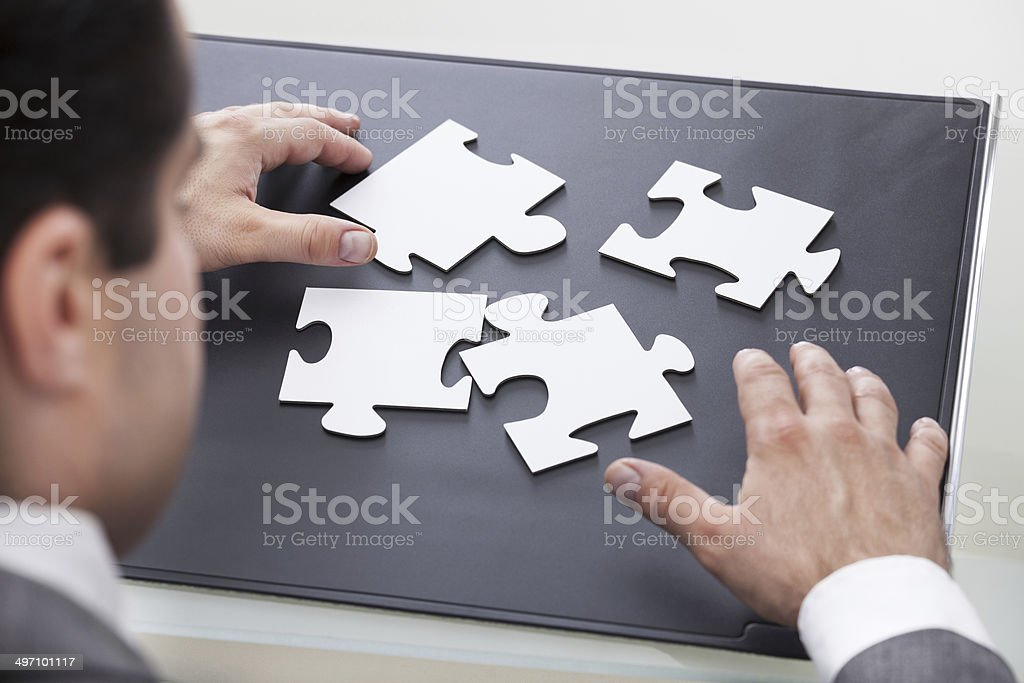 Businessman Solving Puzzle stock photo