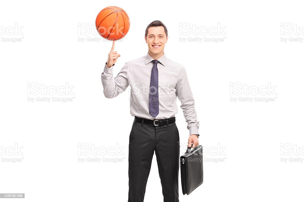 Businessman spinning a basketball on his finger stock photo