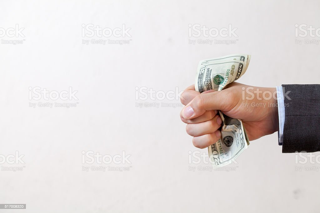 Businessman squeezing bank notes in white isolated stock photo