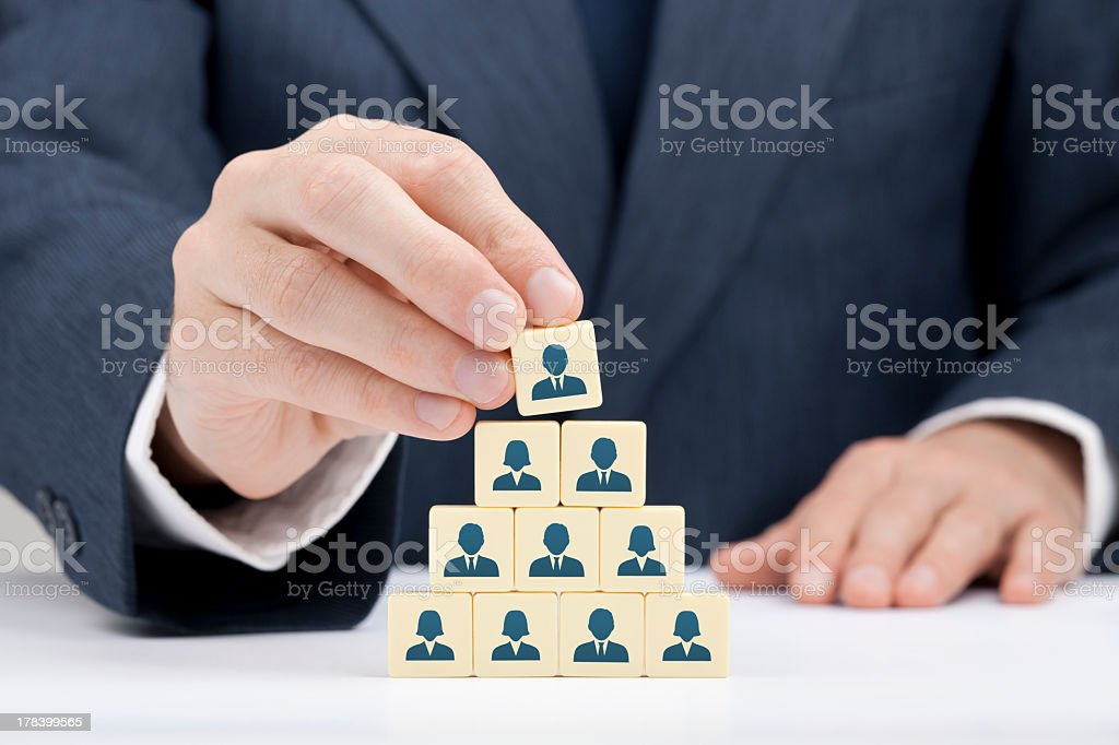 A businessman stacking blocks relating to human resources stock photo