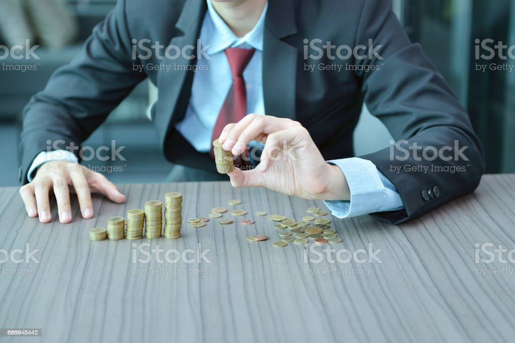 Businessman Stacking Coins in Increasing Order at desk stock photo