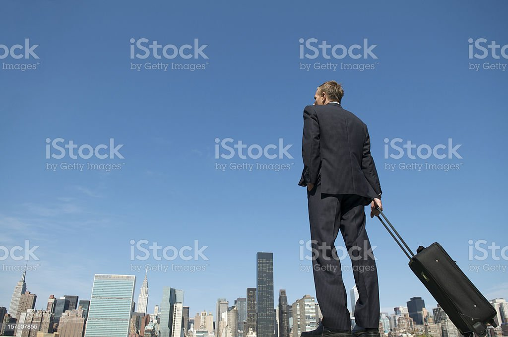 Businessman Standing Above City Skyline with Carry-On Luggage Suitcase royalty-free stock photo