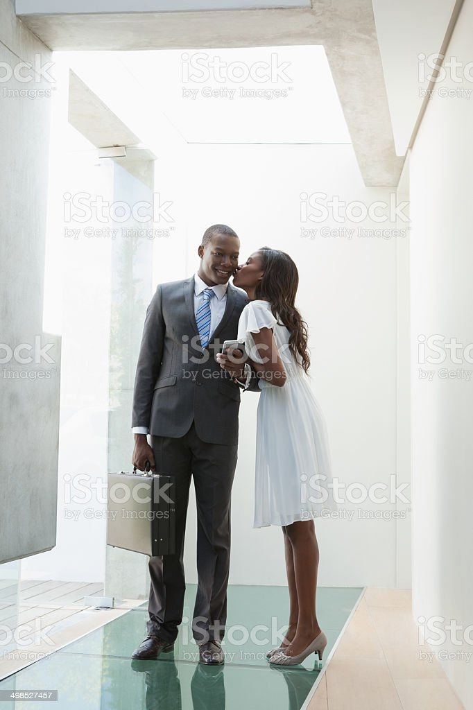 Businessman standing and getting a kiss from his girlfriend royalty-free stock photo