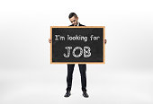 Businessman standing and holding blackboard with words 'I'm looking
