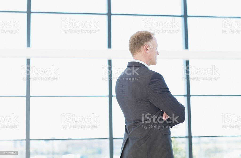 Businessman standing and looking pensively out window royalty-free stock photo