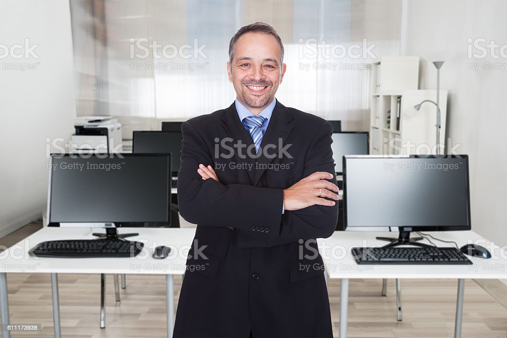 Businessman Standing Arms Crossed In Office stock photo