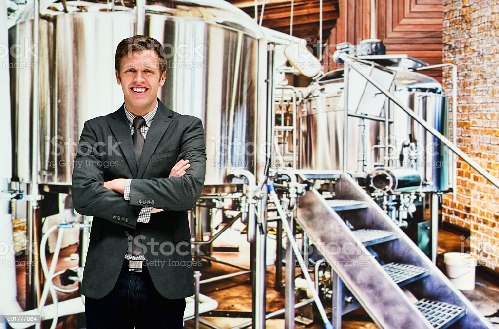 Businessman standing at bottling plant stock photo