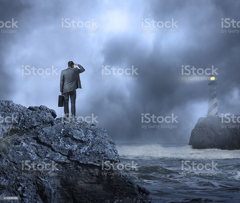Businessman standing at edge of water looking towards a lighthouse stock photo