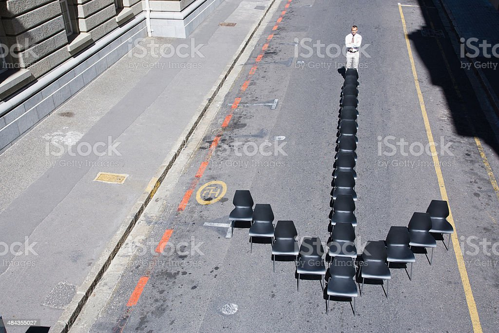 Businessman standing at office chair in arrow-shape stock photo