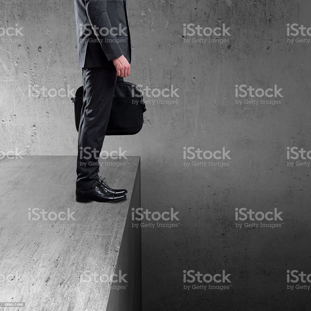 Businessman standing at the edge of wall stock photo