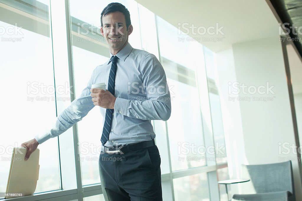 Businessman standing at window in office royalty-free stock photo