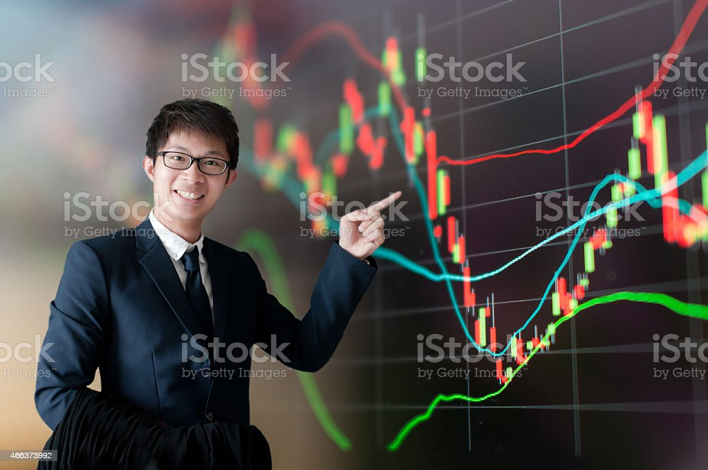 Businessman standing behind a panel with financial statistics. stock photo