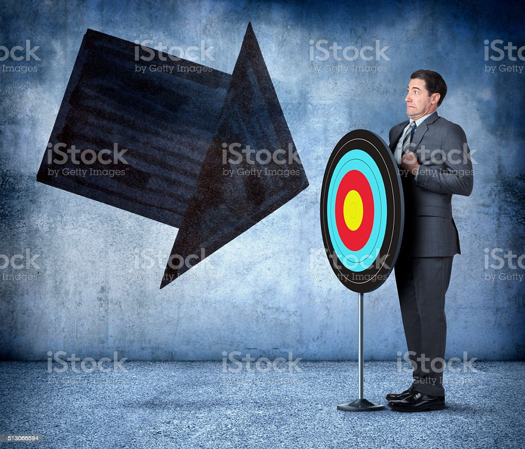 Businessman Standing Behind Target As Arrow Approaches stock photo