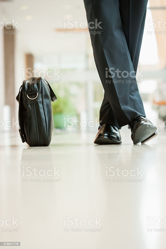 Businessman standing beside his briefcase stock photo