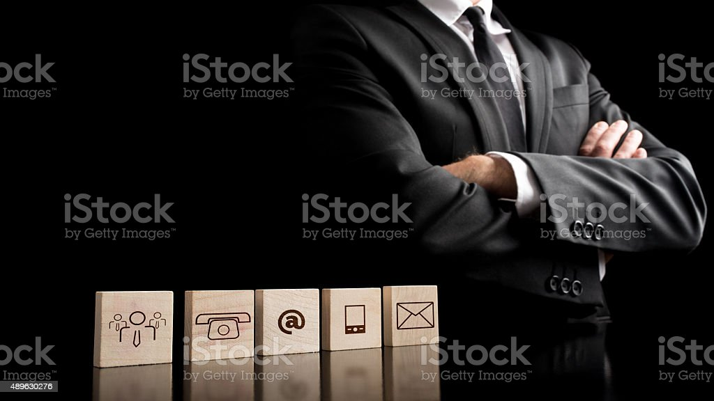 Businessman standing beside wooden blocks with drawings of commu stock photo