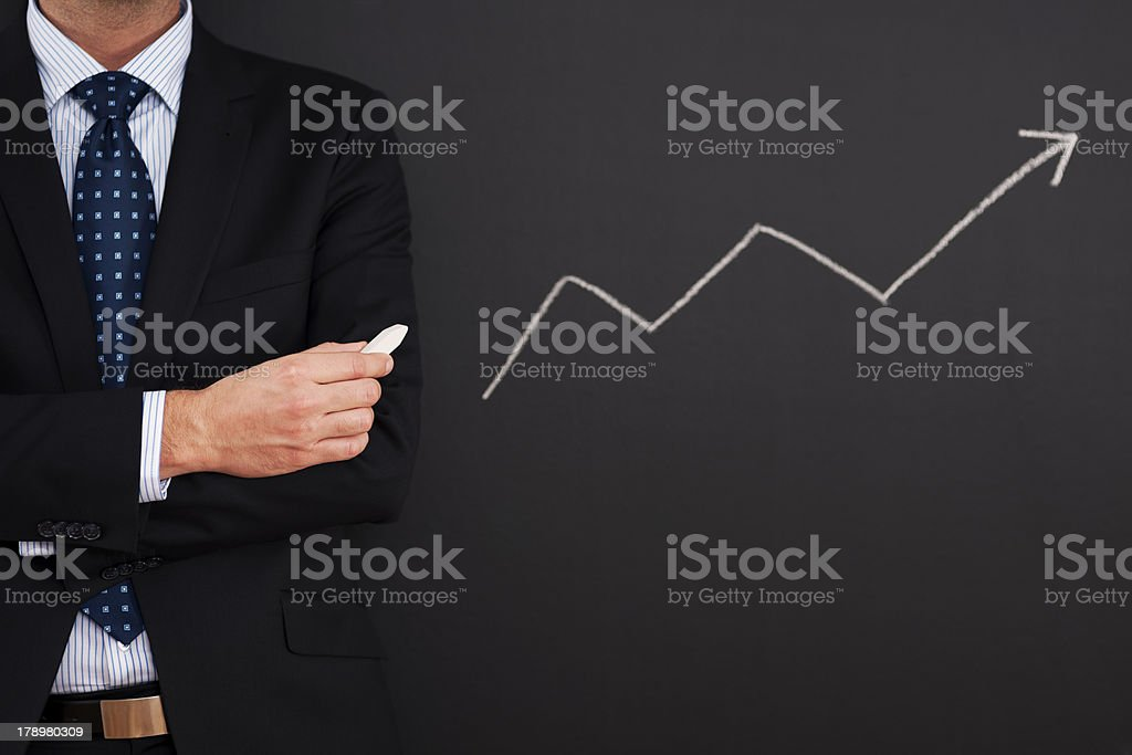 Businessman standing close to arrow sign royalty-free stock photo