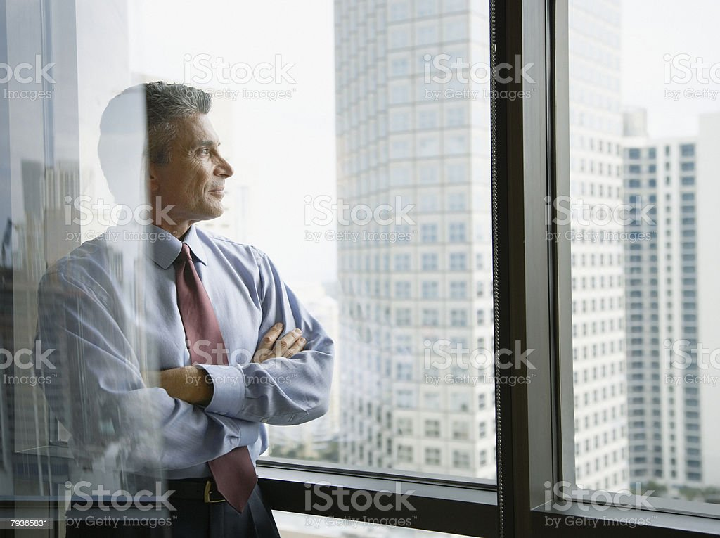 Businessman standing in a corridor by large windows stock photo