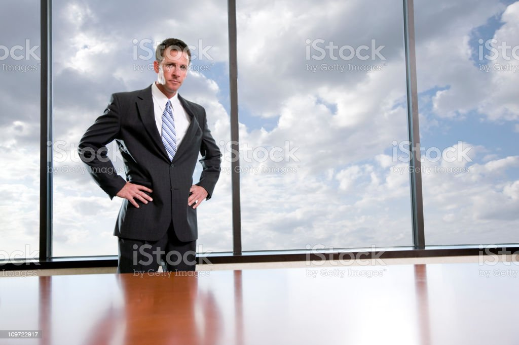 Businessman standing in boardroom, hands on hips stock photo