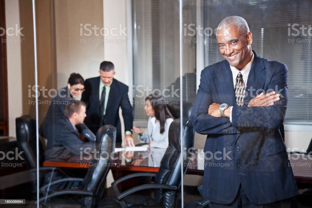 Businessman standing in boardroom with colleagues behind royalty-free stock photo