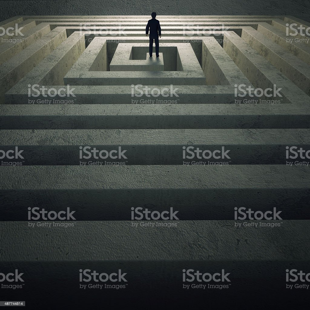 businessman standing in center of labyrinth stock photo