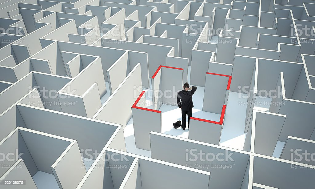 Businessman standing in center of the maze. stock photo