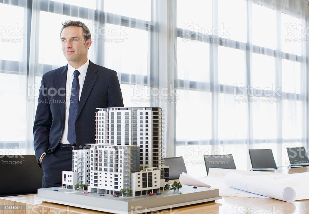 Businessman standing in conference room with model building stock photo