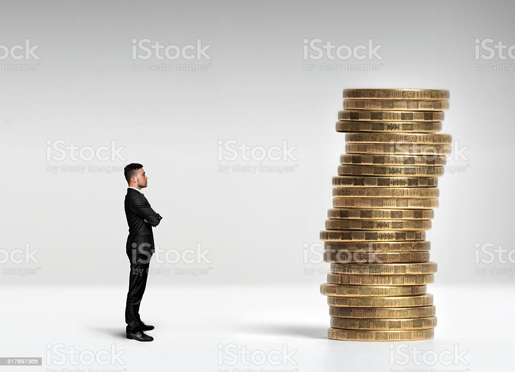 Businessman standing in front of a stack scale rouble coins stock photo
