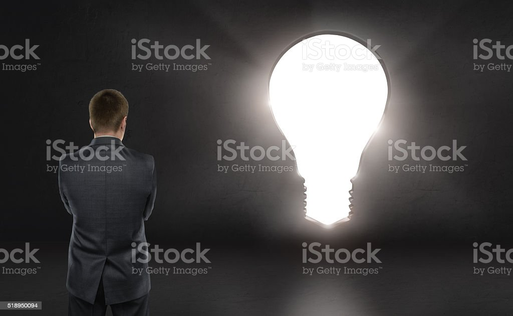 Businessman standing in front of bright big idea light bulb stock photo