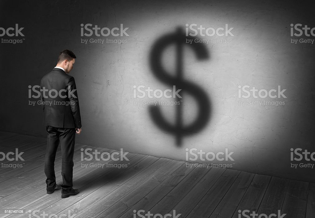 Businessman standing in front of concrete wall on spotlight with stock photo