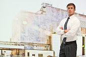 Businessman standing in front of factory