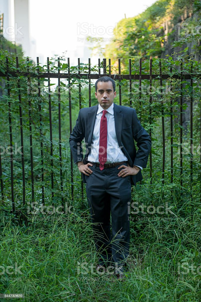 Businessman standing in front of fence in park. stock photo