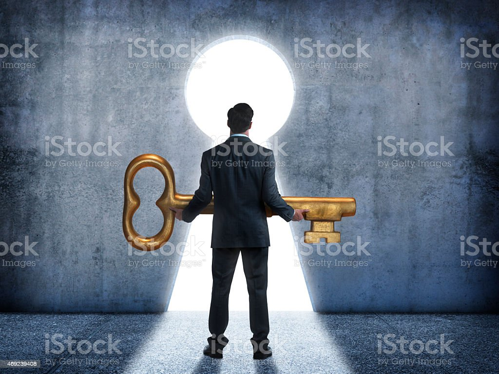 Businessman standing in front of keyhole holding a large key stock photo