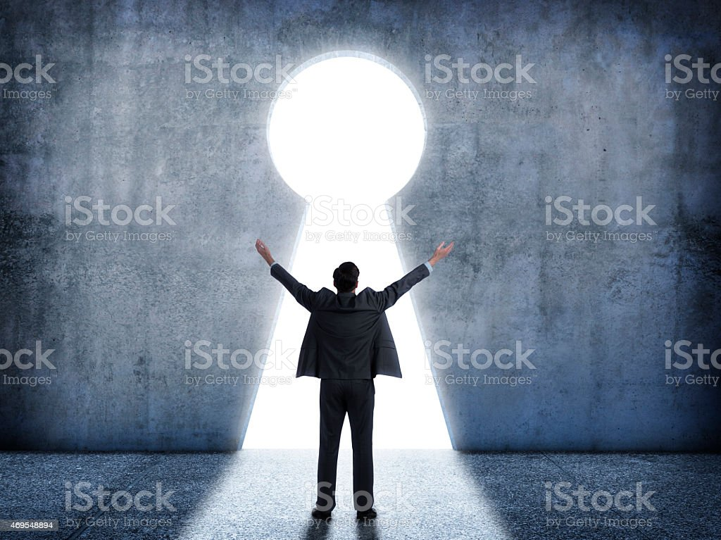 Businessman standing in front of keyhole with his arms raised stock photo
