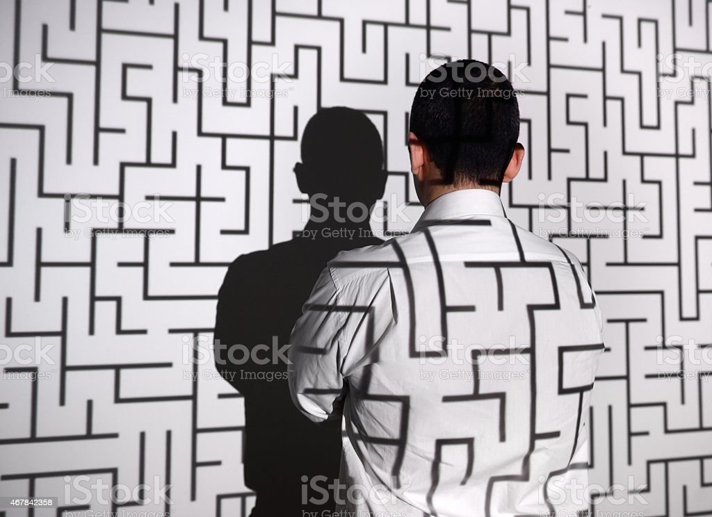 Businessman standing in front of labyrinth stock photo