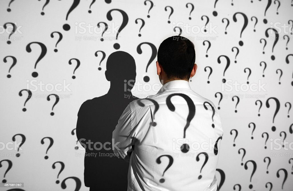 Businessman standing in front of question marks stock photo