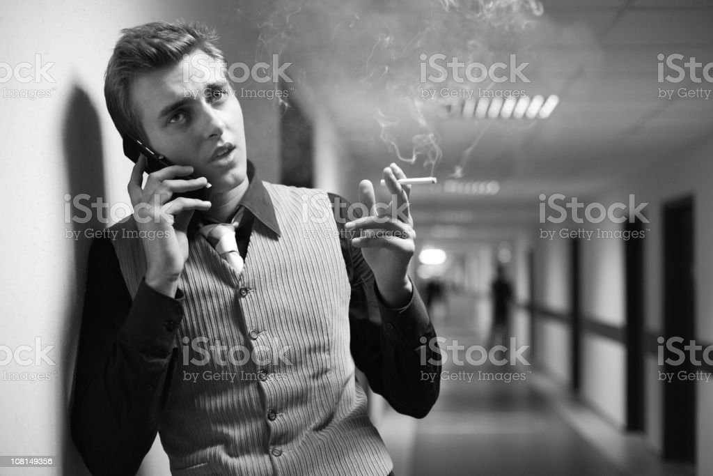 Businessman Standing in Hallway, Smoking and Talking on Cell Phone royalty-free stock photo