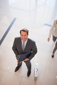 Businessman standing in lobby with briefcase