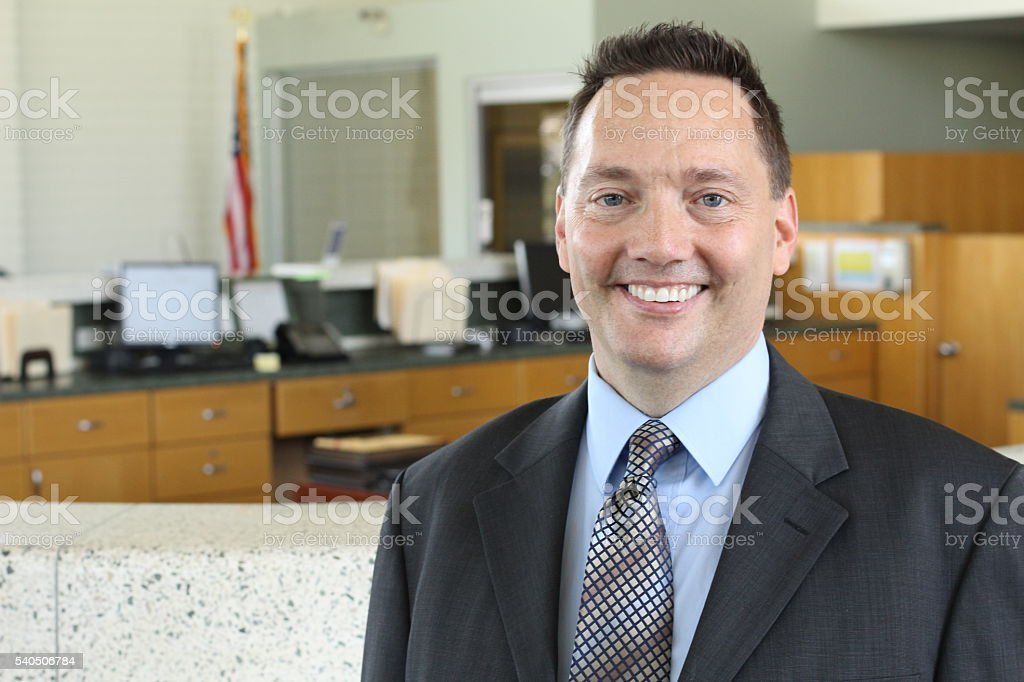 Businessman standing in office and smiling stock photo