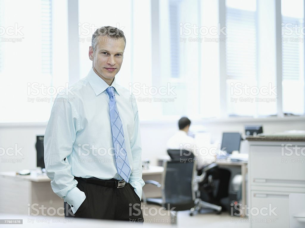 Businessman standing in office smiling with co-worker in background royalty-free stock photo