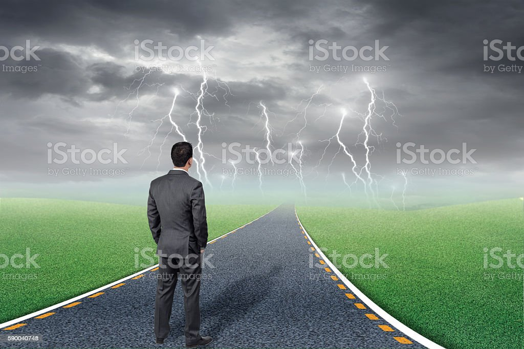 Businessman standing in road leading to storm stock photo
