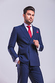 businessman  standing in studio posing with hand in pocket