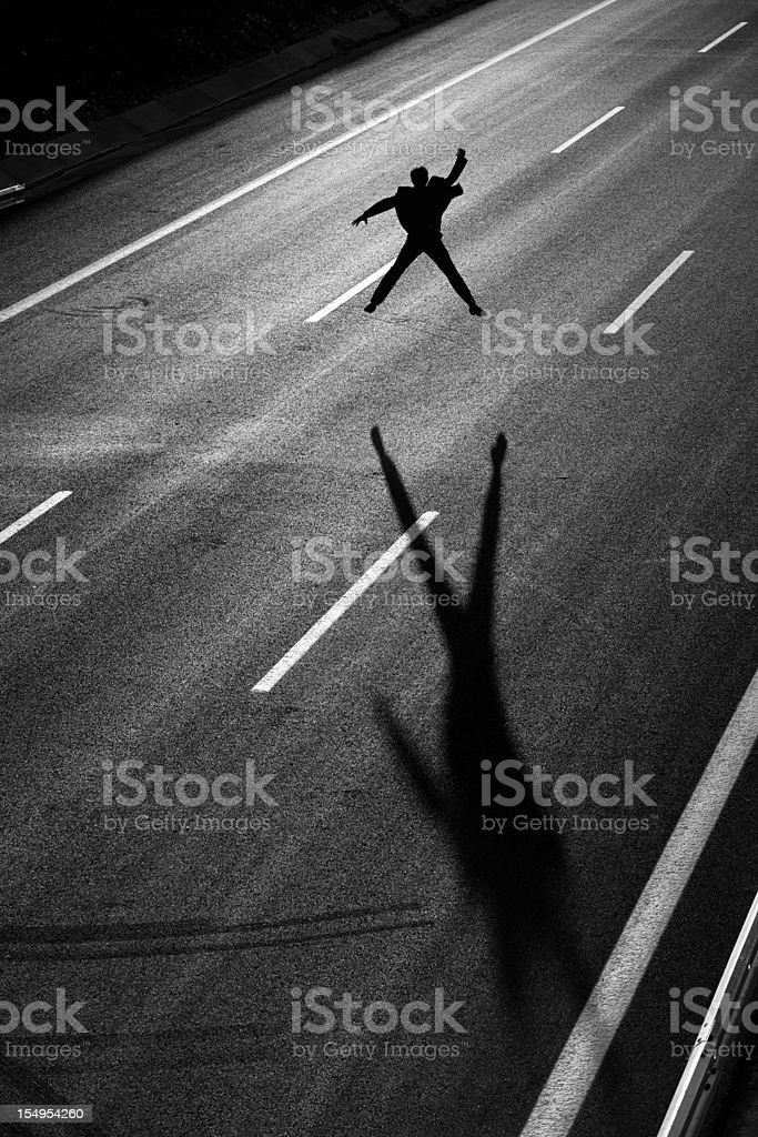 Businessman standing in the middle of highway and stopping traffic royalty-free stock photo