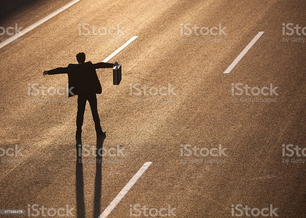 Businessman standing in the middle of highway and stopping traffic stock photo