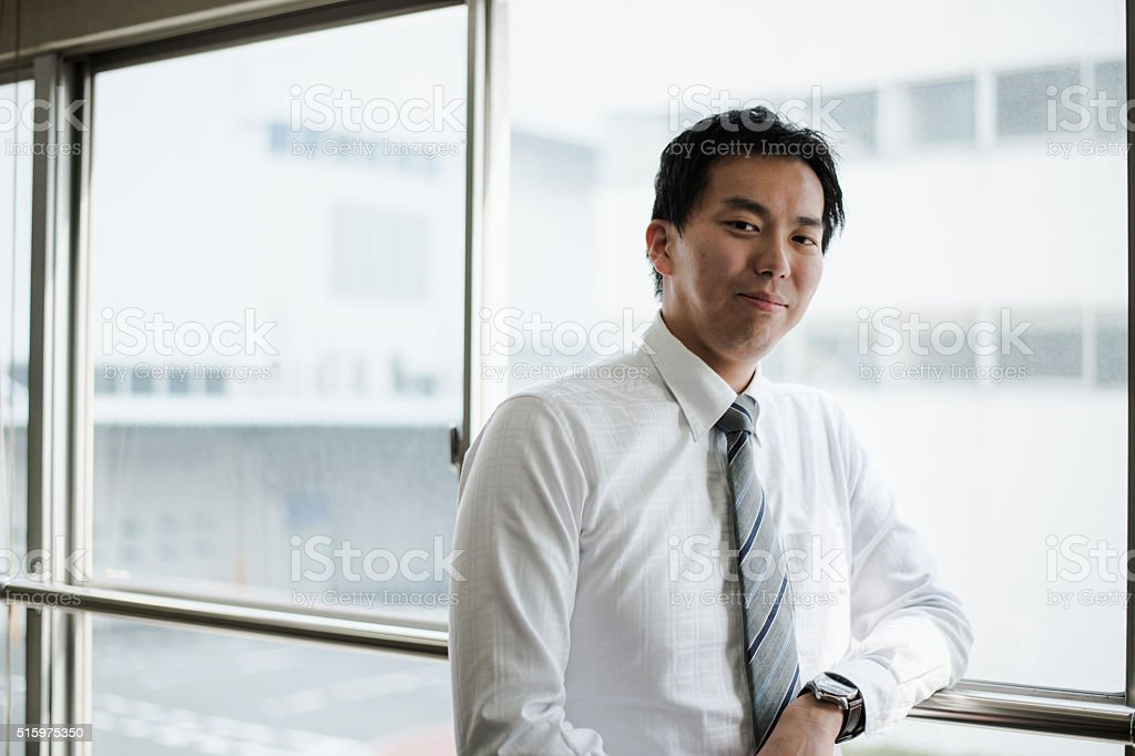 Businessman standing in the office of the window stock photo