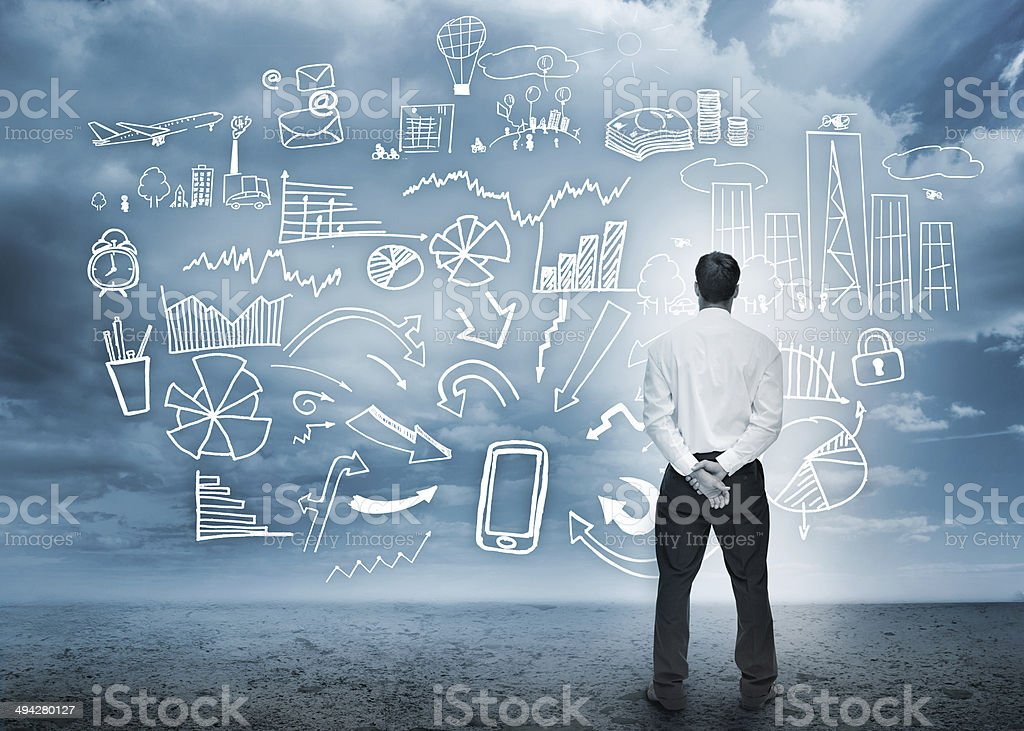 Businessman standing looking at detailed business flowchart stock photo