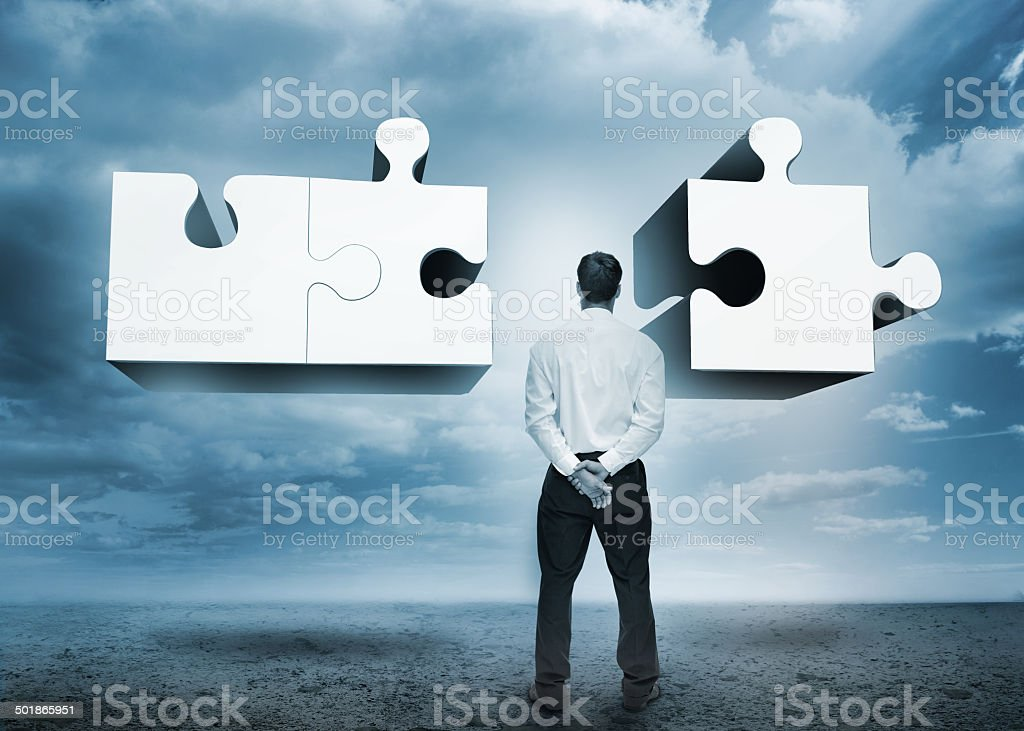 Businessman standing looking at jigsaw puzzle stock photo