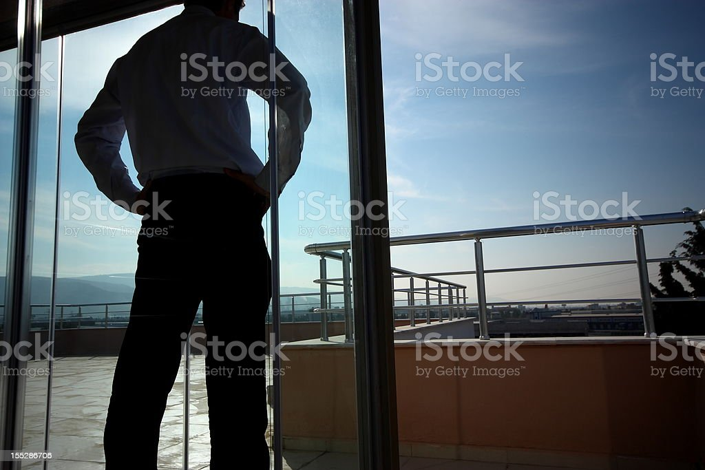 A businessman standing near a glass door royalty-free stock photo