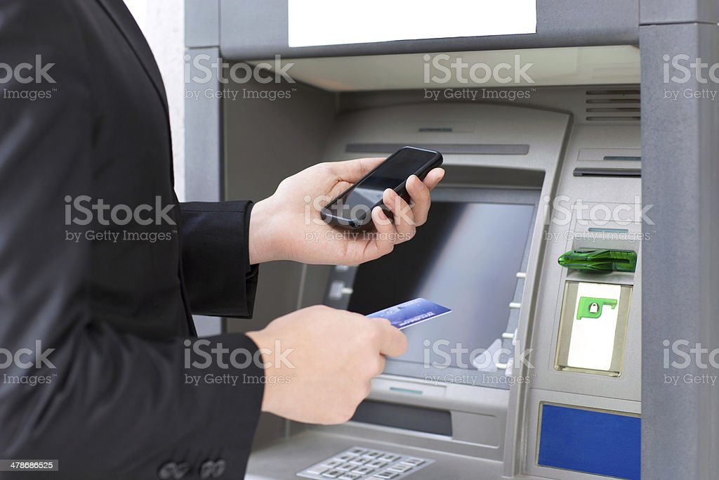 businessman standing near the ATM and holding a credit card stock photo